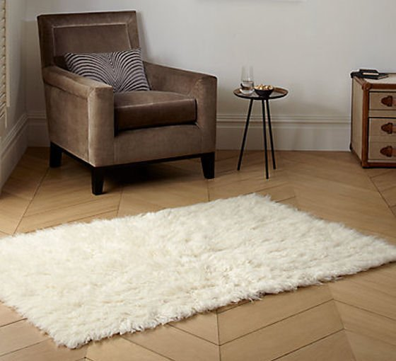 White wool Flokati rug in room setting with brown chair on wooden floor