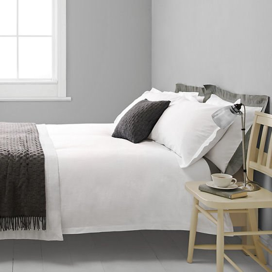 John Lewis Croft Collection Baby Seersucker white cotton bedding with grey blanket and cushion in contemporary bedroom setting