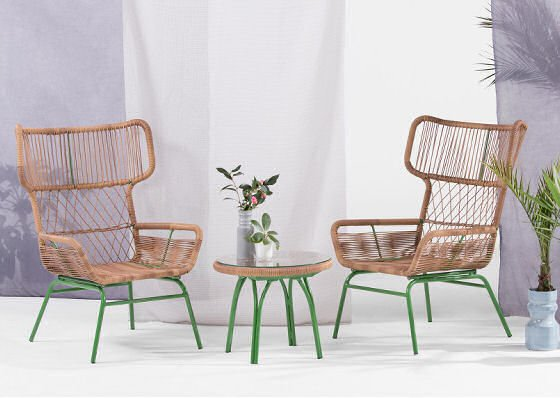 Rattan garden furniture with green frame, rattan armchairs and rattan side table in outdoor room