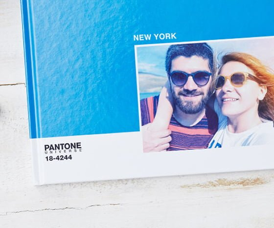 Bright blue Pantone Photobook with New York title and picture of smiling couple