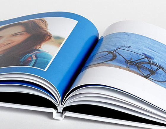 Close up of opened hardback Pantone Photobook with blue pages and images
