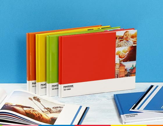 Brightly coloured Pantone Photobooks from Photobox against a cobalt blue wall
