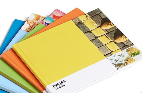 Stack of Photobox Pantone Photobooks with blue, green, orange and yellow covers