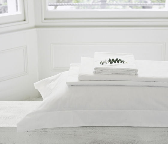 The White Company summer bedlinen folded with eucaplytus sprig on top