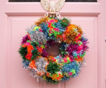 Colourful contemporary Christmas wreath on pale pink front door