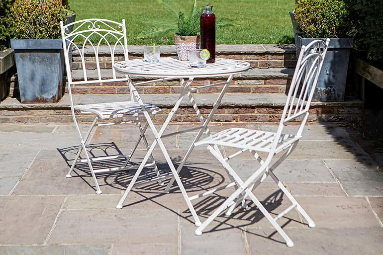 Metal white outdoor bistro table and chairs set on terrace