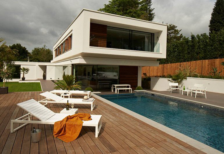 Case Eos contemporary sun loungers on decking by pool outside modernist house