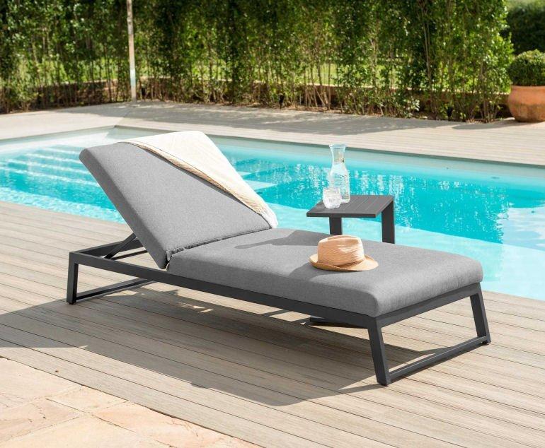 Grey contemporary sun lounger next to pool