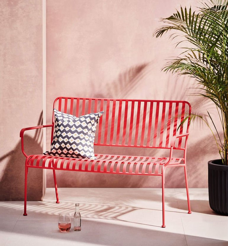 Habitat Indu Garden Bench for small spaces in red metal against pink wall
