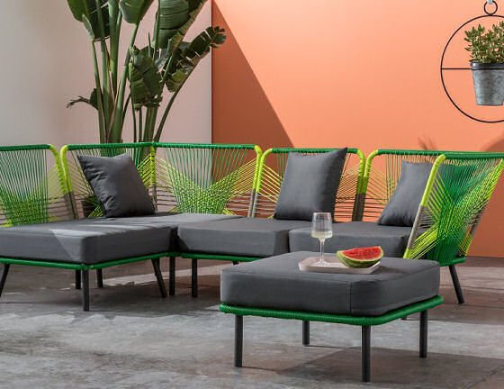 Colourful garden furniture in outdoor room with outdoor corner sofa and footstool