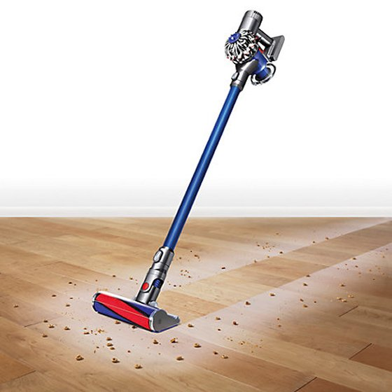 Dyson V6 Fluffy Cordless Vacuum Cleaner on wooden floor with dust and debris