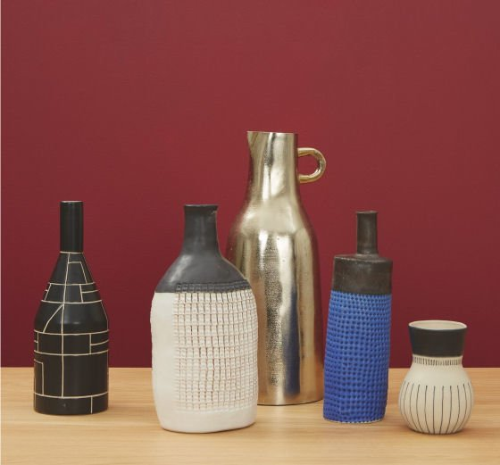 Contemporary bottle vases from Habitat against red background