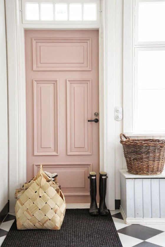 Millenial Pink front door with black wellies and rustic baskets