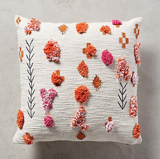 White Heradia cushion with orange and pink tufting and pompoms from Anthropologie