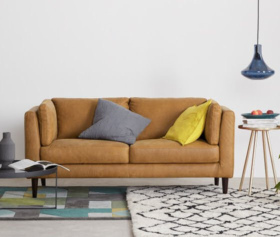 Tan leather sofa for small spaces in contemporary room setting