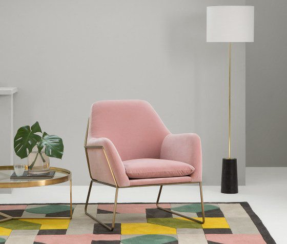 Pink velvet armchair with brass side table, colourful rug and contemporary floor lamp