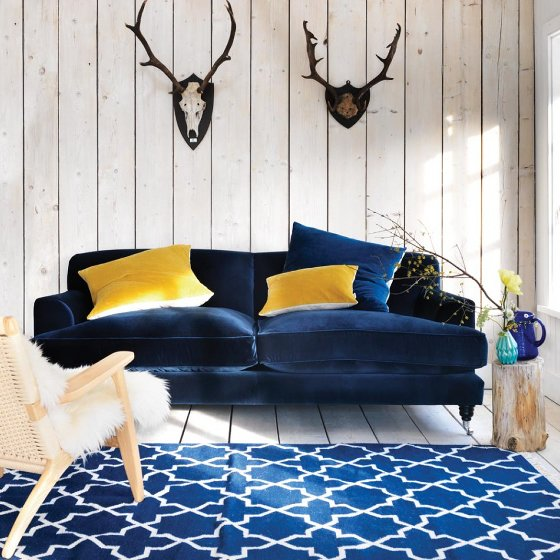 Graham and Green Clio contemporary blue velvet sofa and yellow velvet cushions in room setting