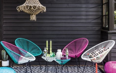 Colourful garden furniture against black wooden wall with boho chandelier