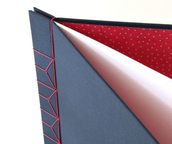 Detail of hardback A4 handbound journal with navy covers, red stab binding and red polka dot lining papers