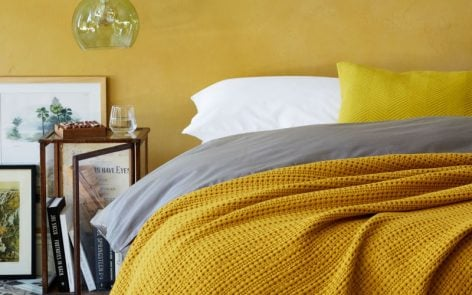 Cotton waffle bedspread on bed with grey bedlinen and yellow wall