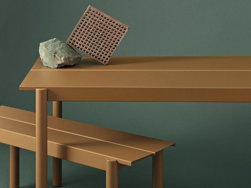 Muuto Linear Garden Table and Bench in Burned Orange against dark green background