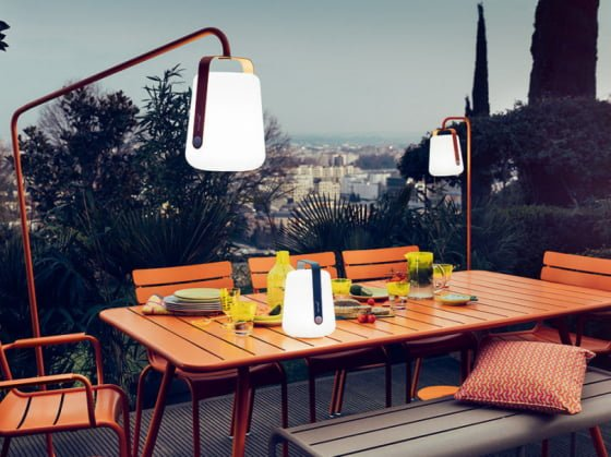 Outdoor lighting ideas for summer and beyond colourful beautiful fermob balad outdoor lanterns hanging from metal frames over orange table on outdoor terrace aloadofball Images