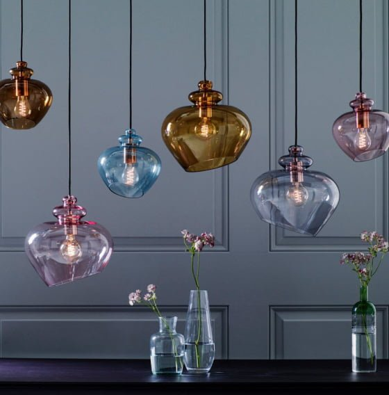 Coloured glass pendant lights by heals against grey panelled wall