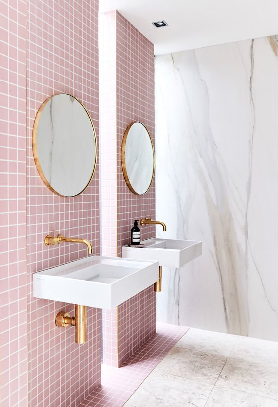 Pink tiled bathroom with white basins, round gold mirrors and matching hardware