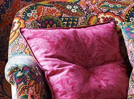Colourful Liberty print upholstered chair with pink cushion