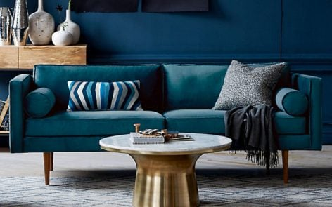 Contemporary marble coffee table with brass base in blue room