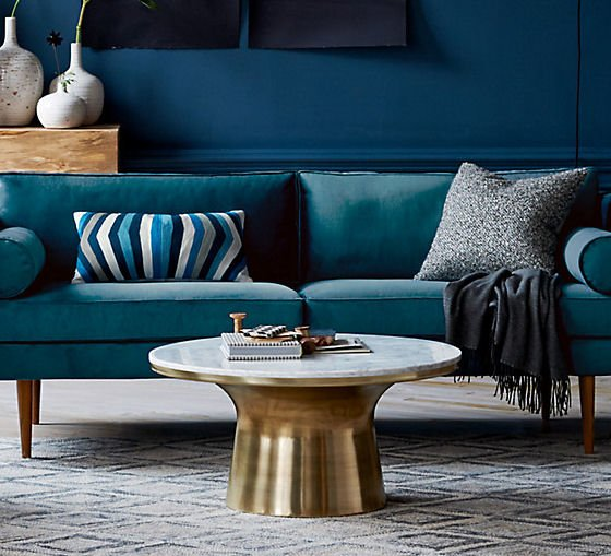 Round marble coffee table with brass pedestal base in front of turquoise sofa and dark blue walls