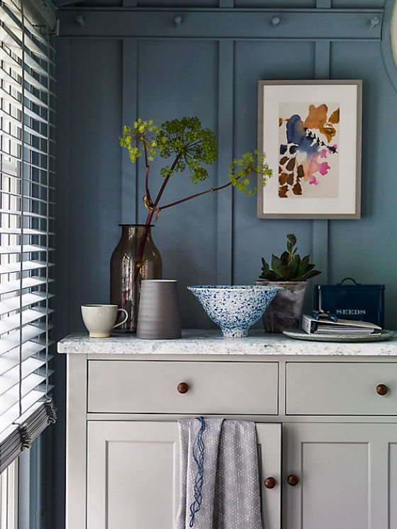 Croft Collection Montrose Sideboard with marble top against blue panelled wall with colourful painting