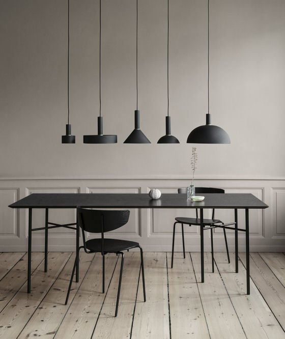 Ferm Living Collect Lighting black and brass contemporary pendant lights hung over black dining table