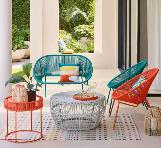 colourful garden furniture in terrace setting, red outdoor chair and table, blue outdoor sofa, grey outdoor table