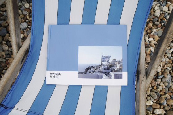 Blue Pantone Photobook on blue and white striped deckchair on pebble beach
