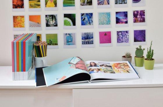 Coloured Photobox Pantone Photobooks on desk with coloured polaroids on wall behind