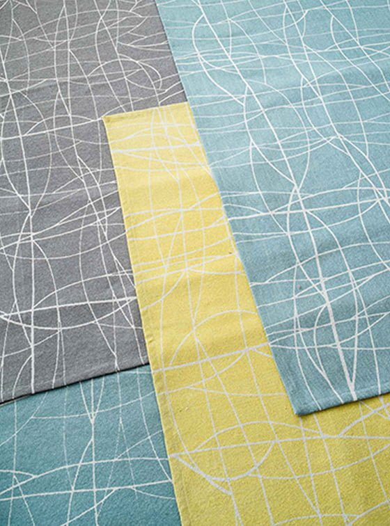 Screen printed cotton Chacha rugs in teal, yellow and grey