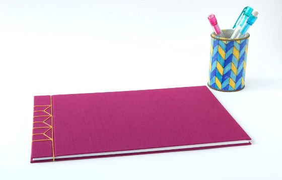 Fuschia pink handmade journal with yellow linen stab binding and colourful pen pot