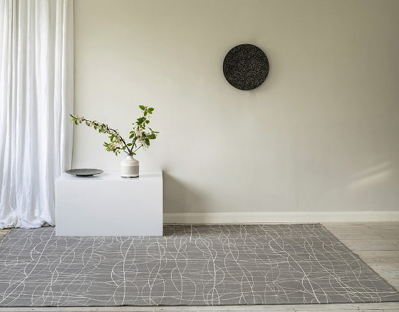 Grey and white screen printed Chacha rug with white table, vase and greenery