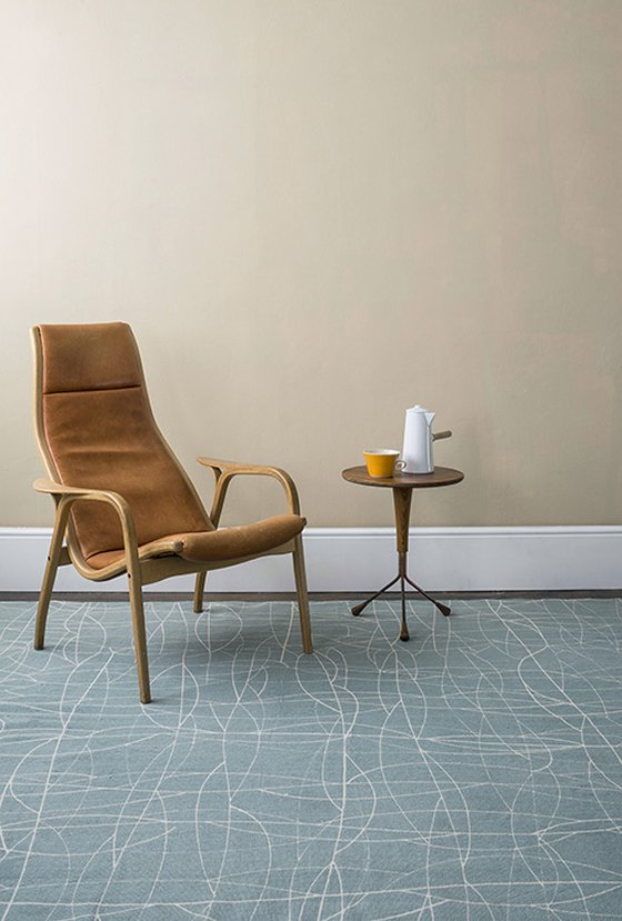 Screen printed Chacha rug in teal blue with leather midcentury chair and side table