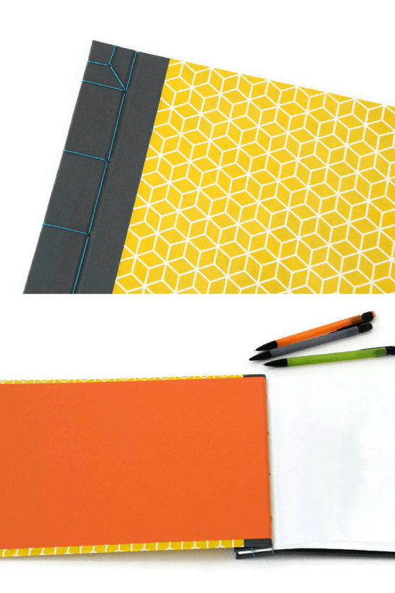 Detail of handmade journals with grey bookcloth, yellow lokta paper and blue linen stab binding