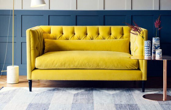 Heal's Balmoral contemporary velvet sofa in yellow velvet against blue panelledwall