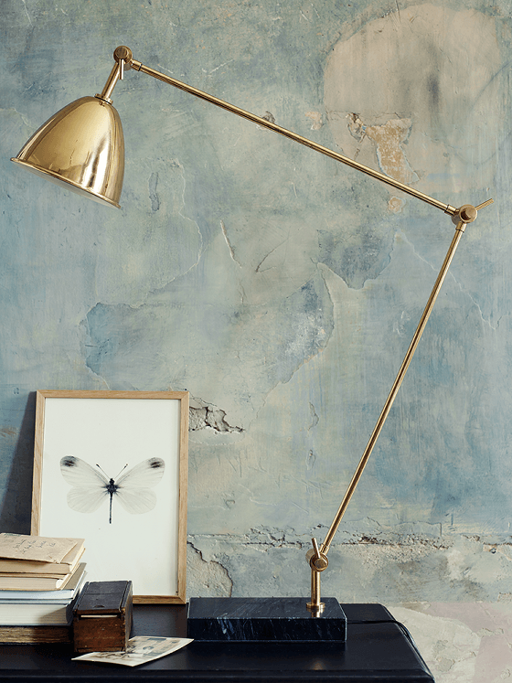 Marble and brass desk lamp against blue distressed plaster wall
