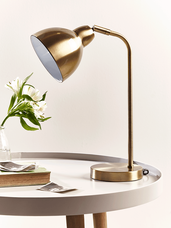 Brass desk lamp on blush pink table with flowers and book