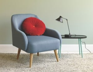blue compact armchair for small spaces with red cushion and side table with lamp