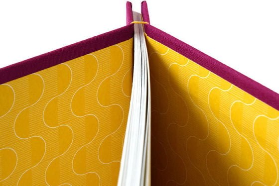 Detail of stab bound handmade journal showing yellow patterned lining papers