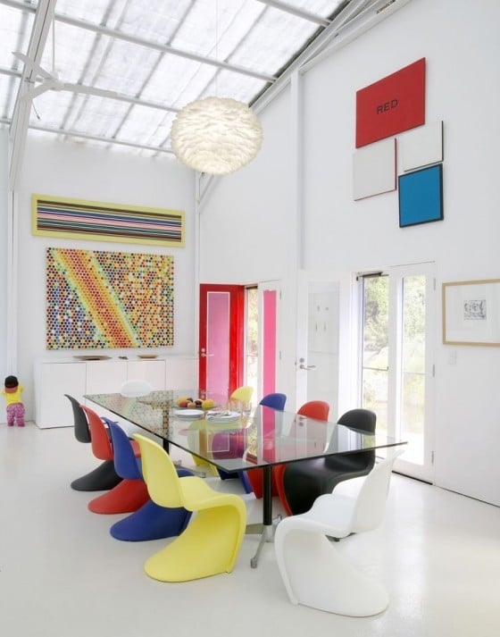 Eos feather pendant lamp hung in white contemporary room with glass table and coloured Panton chairs