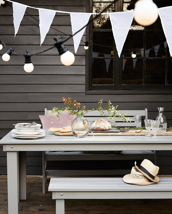 Extendable festoon outdoor lights with white bunting and outdoor eating setting