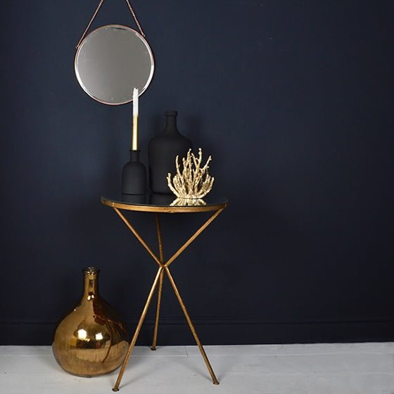 dark blue wall with brass mirror and side table