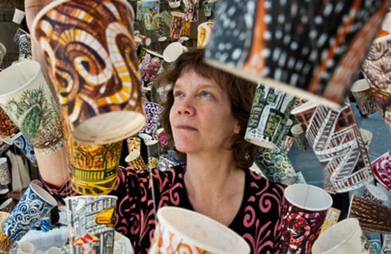 Artist Gwyneth Leech surrounded by her painted coffee cups